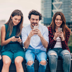 Multi-ethnic group of people sitting on an urban bridge text messaging and sharing smart phone content.