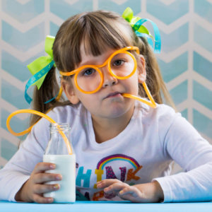 Girl drinking milk with funny glasses plastic straw